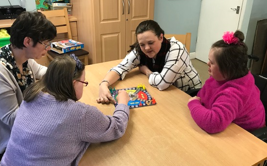 Care worker playing a board game with three residents.