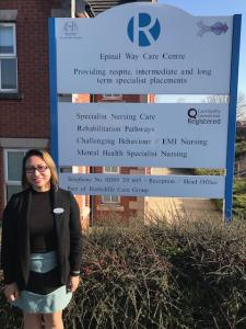 Registered care manager posing in front of the residential care home that she manages.